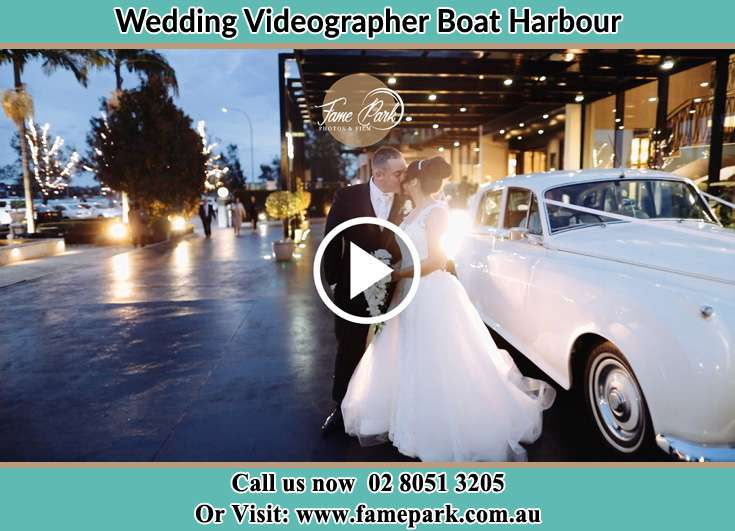 The new couple kissing near the bridal car Boat Harbour NSW 2316